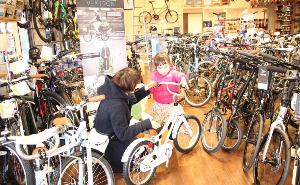 店内で自転車を選ぶ女の子